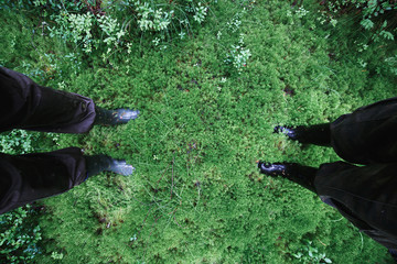Male and female feet in rubber boots in thick moss