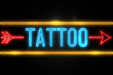 Tattoo  - fluorescent Neon Sign on brickwall Front view