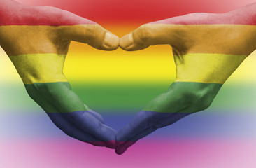 Hands painted as the rainbow flag forming a heart, symbolizing gay love