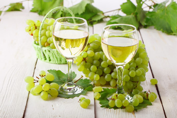 Glasses with white wine and fresh grapes on a wooden table.