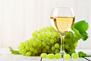 A glass of white wine and fresh grapes on a wooden table.