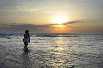 Silhouette of young beautiful asian woman standing on water free and relaxed looking at sun horizon on sunset beach