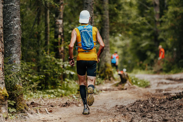 Fototapete - male runner with backpack and cap running woods marathon