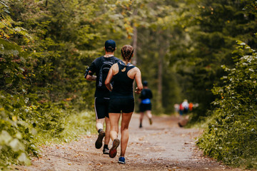 Fototapete - young man and woman running at forest trail marathon