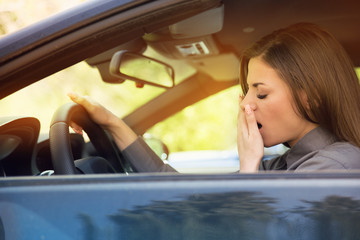 sleepy fatigued yawning young woman driving her car