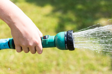 Young girl hand spraying green grass using garden hose and sprinkler