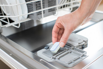 Close Up Of Woman Putting Detergent Tablet Into Dishwater