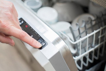 Close Up Of Woman's Hand Pressing Start Button On Dishwasher