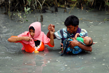 Rohingya refugees carry their child as they walk through water after crossing border by boat through the Naf River in Teknaf, Bangladesh