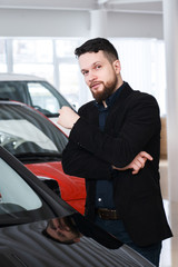 man chooses the car in the showroom