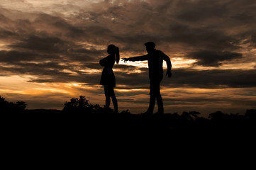 Silhouette couple in love ,man and women are quarrel in nature ,sky with clouds in sunset time,pastel and vintage tone