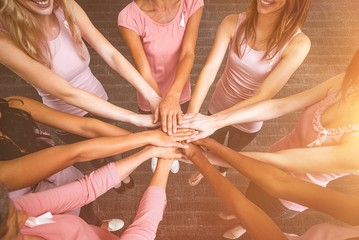 Composite image of women in pink outfits joining in a circle for