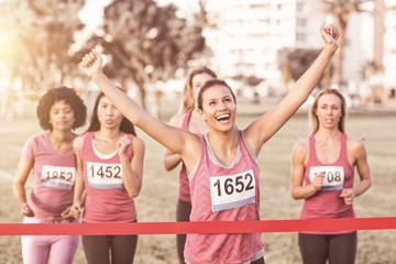 Cheering brunette winning breast cancer marathon