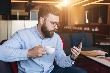 Young serious attractive bearded businessman in blue shirt and glasses sits on sofa in cafe, drinks coffee and uses smartphone