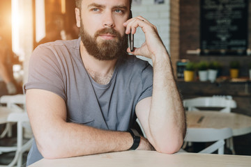 Front view. Portrait of attractive young bearded hipster man sitting in cafe at table and talking on his cell phone.