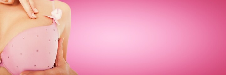 Composite image of mid section of woman wearing pink bra for