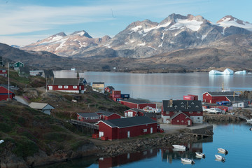 Colorful town in Greenland on harbor and snowy mountains in background