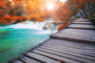 Wooden path across beautiful sunny autumn lake