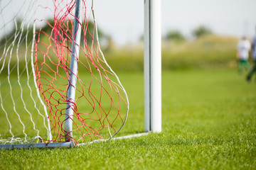 Football goal detail with a soccer players in the background. Football soccer pitch. Soccer goal post and net detail on green turf