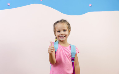 Adorable little girl with school bag showing thumbs up, copy space