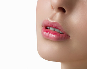 The slightly opened mouth with white teeth. Gentle pink gloss of lipstick on lips. A macro shot of natural cosmetics on a white background. Cosmetology, cosmetics, fashion