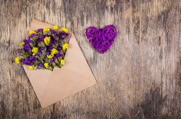 Dry wild flowers in an envelope and a wicker heart. Romantic concept. Copy space