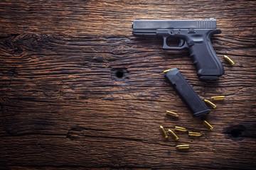 Gun pistol. 9 mm pistol gun and bullets strewn on the rustic oak table