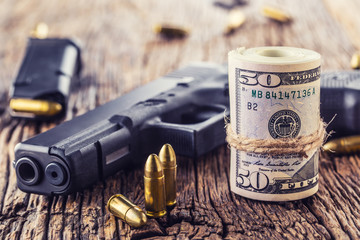 Gun and money. 9 mm pistol gun bullets strewn and roll dollar banknotes on rustic oak table