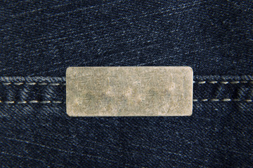 Denim blue fabric with one small rectangular metal label for your text. The texture is a close-up macro shot.