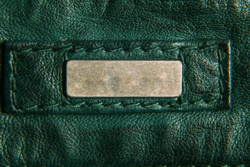 Detail of leather green jacket. A metal label for your text. Close-up, macro texture.
