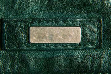 Detail of leather green jacket. Metal label. Close-up, macro texture.