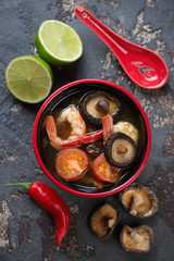 Top view of Tom Yum thai soup with some of its cooking components, vertical shot