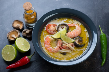 Thai green curry soup with addition of shrimps and shiitake served in a dark gray plate, studio shot