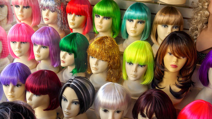 Mannequins Wearing Colorful Wigs in Window of Wig Shop