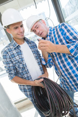 friendly master electrician and apprentice working with loads of wiring