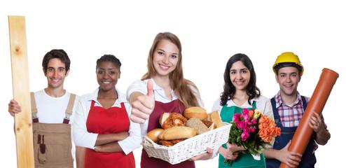 Erfolgreiche Bäckereiverkäuferin zeigt Daumen mit anderen Azubis