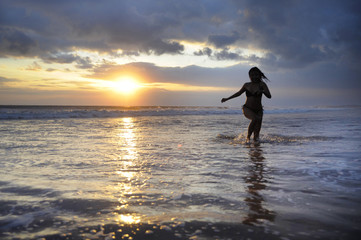 Silhouette of young beautiful and sexy asian woman running free and happy having fun at sunset beach in Bali