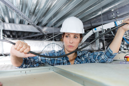 female electrician wiring in building ceiling