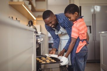 Father taking tray of fresh cookies out of oven with son in