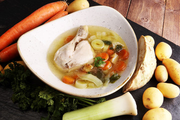 Bone broth made from chicken with carrots, onions various fresh vegetables in a pot - colorful fresh clear spring soup. Rural kitchen scenery bouillon or stock