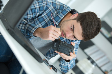 young handsome technician examining and repairing dslr camera