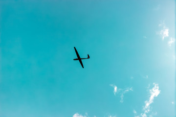 The glider gliding in the blue sky