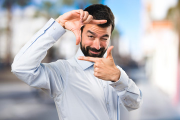 Handsome man with beard focusing with his fingers on unfocused background