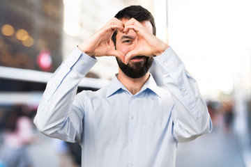 Handsome man with beard making a heart with his hands on unfocused background
