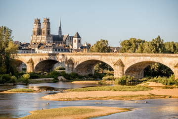 Landscape view on the river and old arch bridge in Orleans city during the sunset in France