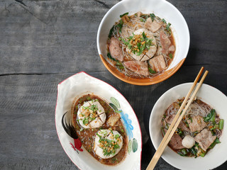 thai noddle of jumbo pork ball, pig liver, pork slide and vegetable on wooden table, hot noodle with blood pink for soup, in Thailand call Boat Noddle.