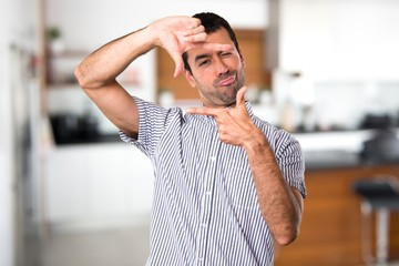 Handsome man focusing with his fingers inside house