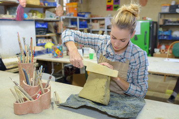 woman sculpts clay crafts pottery class