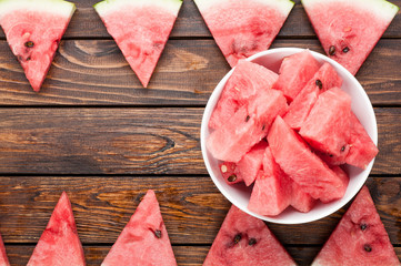 watermelon slices in plate on dark wooden background top view