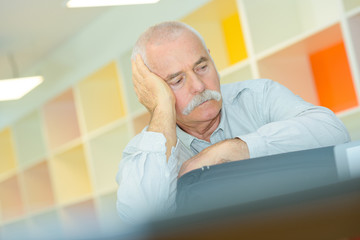 elderly man with hand on his temple has a headache